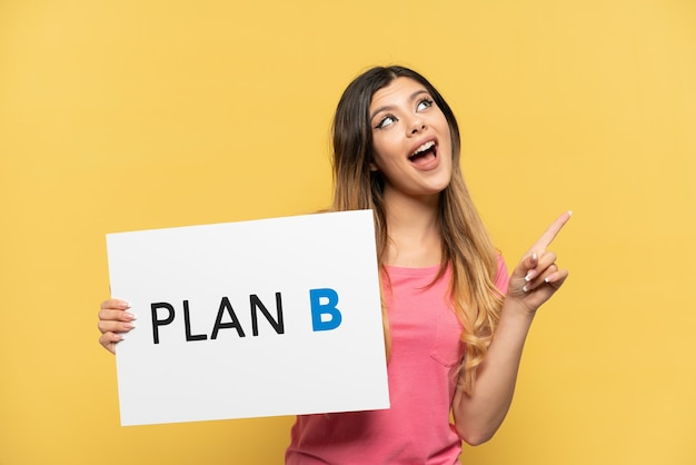 Young russian girl isolated on yellow background holding a placard with the message plan b and thinking