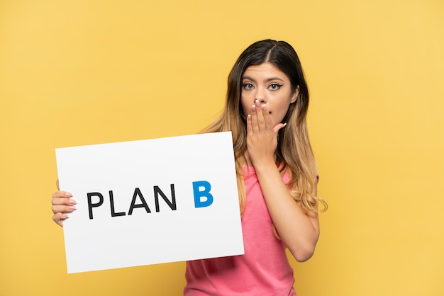 Young russian girl isolated on yellow background holding a placard with the message plan b with surprised expression