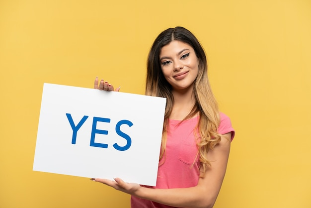Young russian girl isolated on yellow background holding a placard with text yes with happy expression