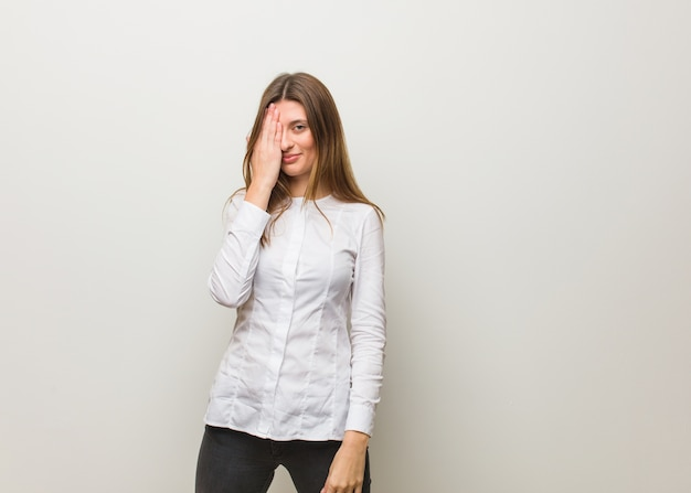 Молодая русская девушка кричит счастливая и держит лицо рукой