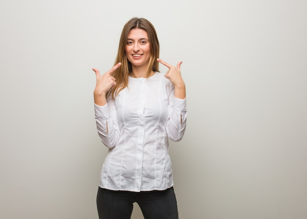 Young russian girl smiles, pointing mouth