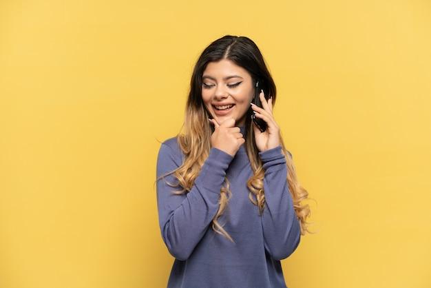 Молодая русская девушка с помощью мобильного телефона на желтом фоне смотрит в сторону и улыбается