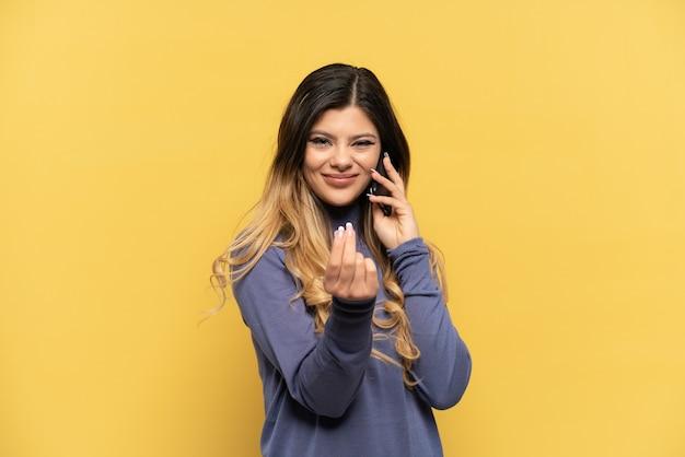 Молодая русская девушка с помощью мобильного телефона, изолированного на желтом фоне, делая денежный жест