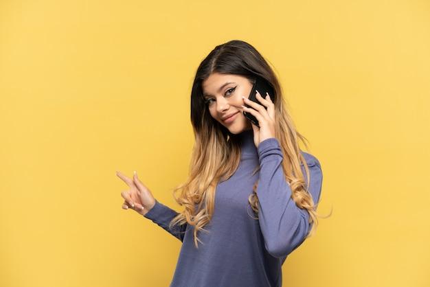 뒤를 가리키는 노란색 배경에 격리된 휴대전화를 사용하는 러시아 소녀