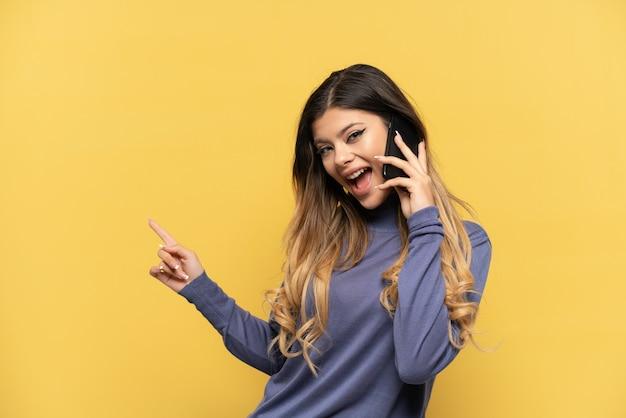 Молодая русская девушка с помощью мобильного телефона изолирована на желтом фоне, указывая пальцем в сторону и представляет продукт