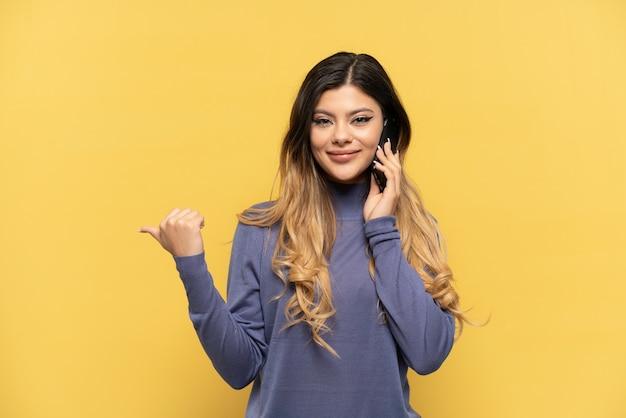 製品を提示する側を指している黄色の背景に分離された携帯電話を使用して若いロシアの女の子