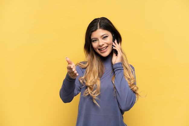 노란색 배경에 격리된 휴대폰을 사용하는 러시아 소녀는 좋은 거래를 성사시키기 위해 악수를 하고 있다