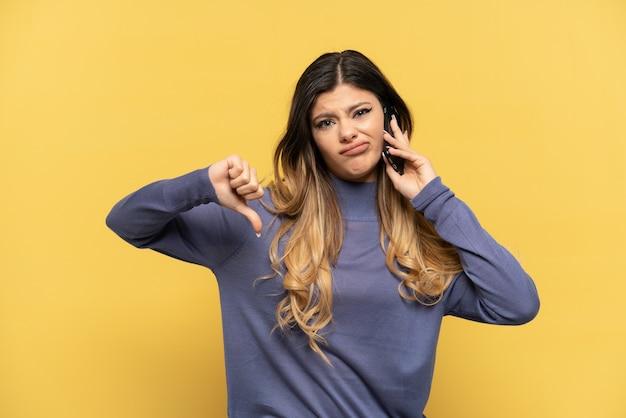 Молодая русская девушка с помощью мобильного телефона изолирована на желтом фоне, показывая большой палец вниз с негативным выражением лица