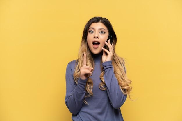 손가락을 가리키는 아이디어를 생각하는 노란색 배경에 고립 된 휴대 전화를 사용하는 젊은 러시아 소녀