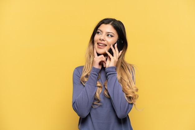 노란색 배경에 격리된 휴대전화를 사용하는 러시아 소녀는 올려다보는 동안 아이디어를 생각하고 있다