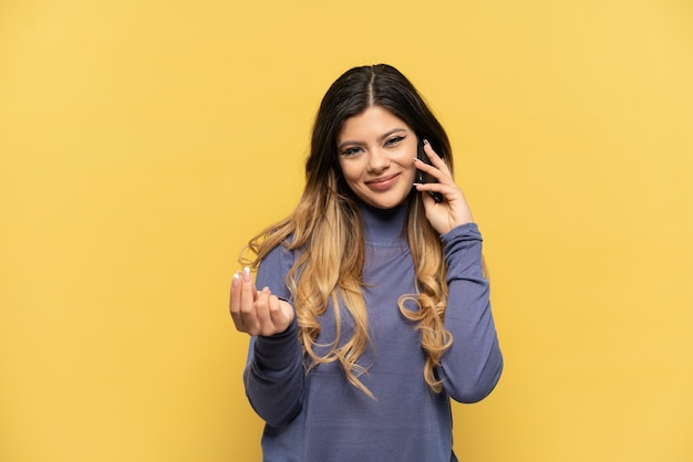 Young russian girl using mobile phone isolated on yellow background making money gesture