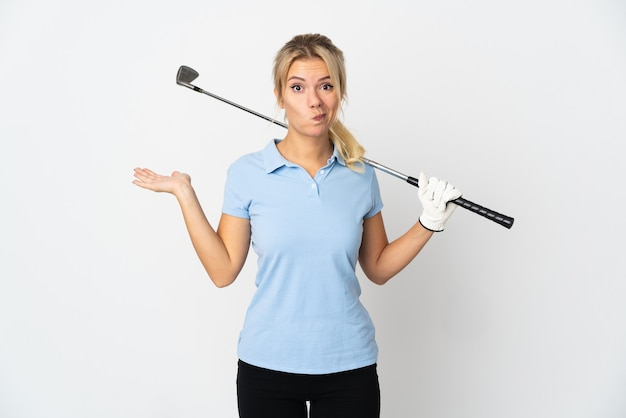 Молодая русская гольфистка изолирована на белом фоне, сомневаясь, поднимая руки