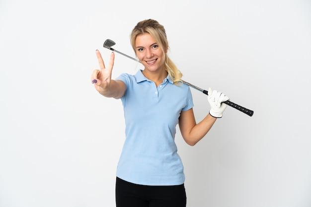 Молодая русская гольфистка, изолированная на белом фоне, улыбается и показывает знак победы