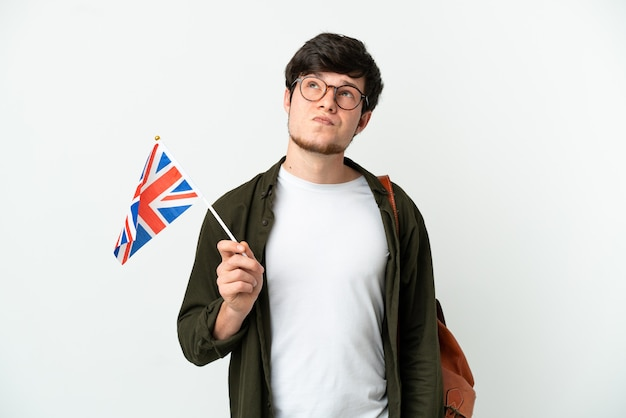 Молодой русский мужчина держит флаг соединенного королевства на белом фоне и смотрит вверх