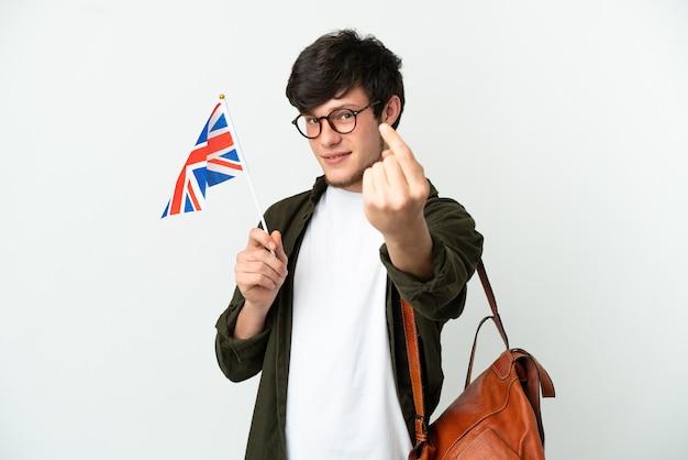 Молодой русский мужчина держит флаг соединенного королевства на белом фоне, делая приближающийся жест