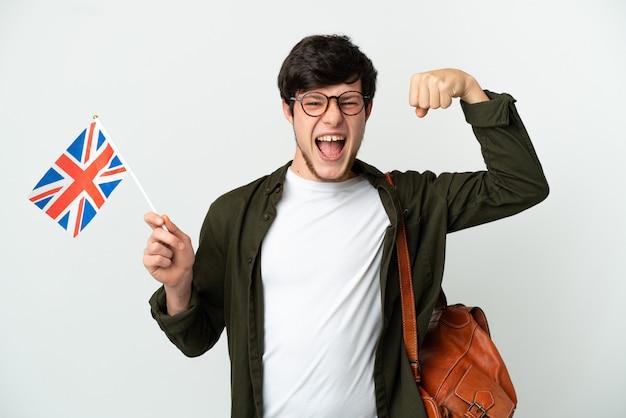 Молодой русский мужчина держит флаг соединенного королевства, изолированные на белом фоне, делает сильный жест