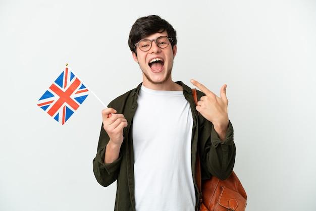 Молодой русский мужчина держит флаг соединенного королевства, изолированные на белом фоне, показывает палец вверх