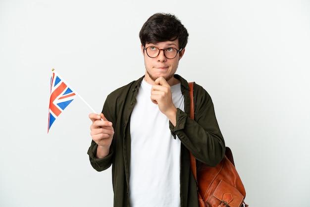 Молодой русский мужчина держит флаг соединенного королевства на белом фоне, сомневаясь и думая