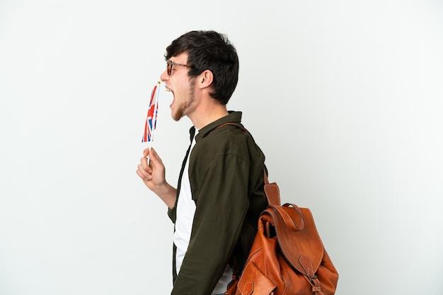 Молодой российский мужчина держит флаг соединенного королевства на белом фоне, смеясь в боковом положении