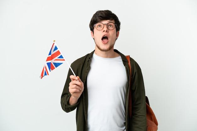 Молодой русский мужчина держит флаг соединенного королевства на белом фоне, глядя вверх и с удивленным выражением лица