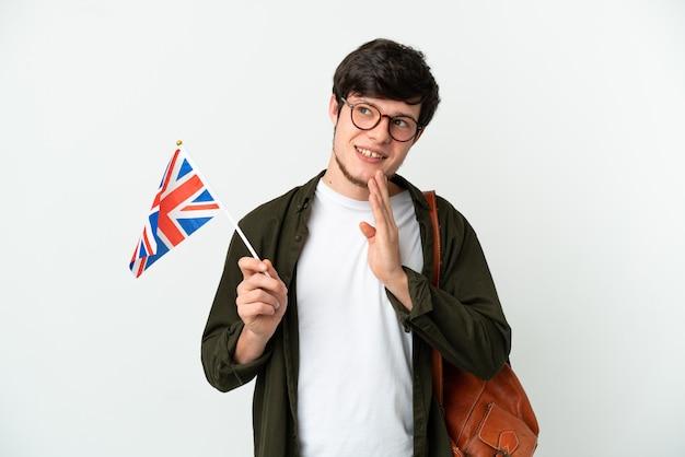 Молодой российский мужчина держит флаг соединенного королевства на белом фоне, глядя вверх, улыбаясь