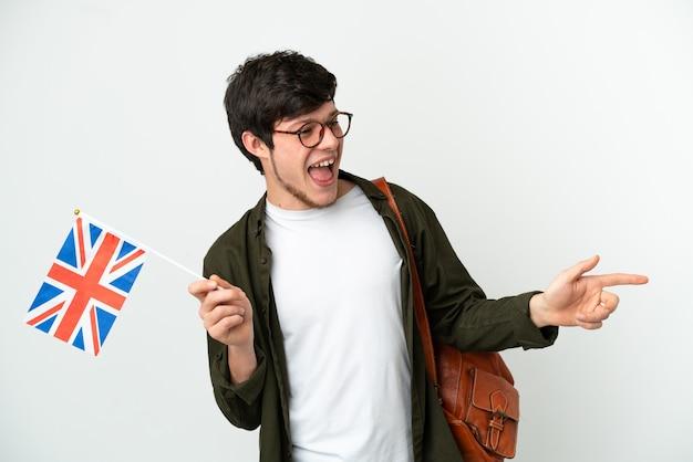 Молодой русский мужчина держит флаг соединенного королевства на белом фоне, указывая пальцем в сторону и представляет продукт