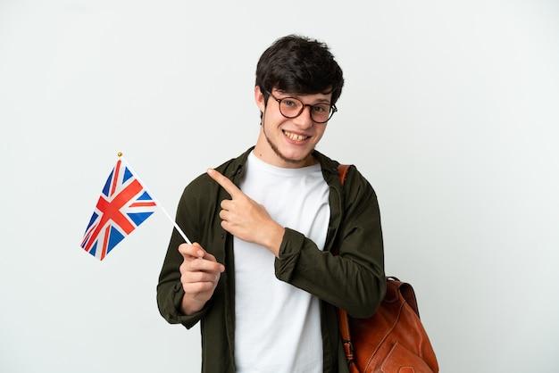 Молодой русский мужчина держит флаг соединенного королевства на белом фоне, указывая в сторону, чтобы представить продукт