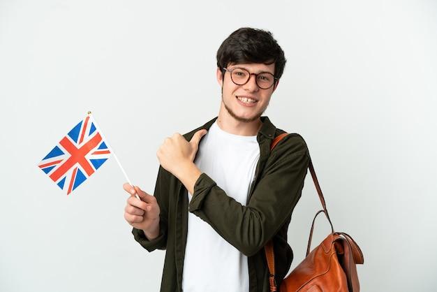 Молодой русский мужчина держит флаг соединенного королевства на белом фоне, гордый и самодовольный