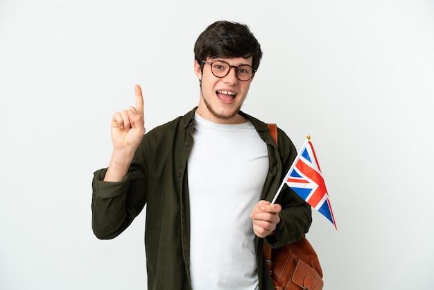 Молодой русский мужчина держит флаг соединенного королевства на белом фоне, показывая и поднимая палец в знак лучших