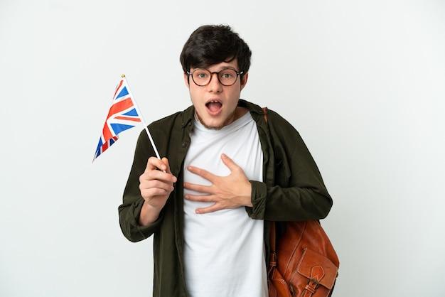 Молодой российский мужчина держит флаг соединенного королевства на белом фоне удивлен и шокирован, глядя вправо