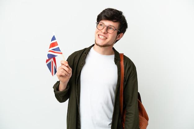 Молодой русский мужчина держит флаг соединенного королевства на белом фоне, думая об идее, глядя вверх