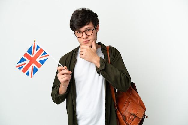 Молодой русский мужчина держит флаг соединенного королевства на белом фоне, думая