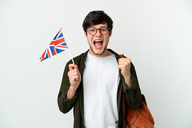 Young russian man holding an united kingdom flag isolated on white background celebrating a victory in winner position