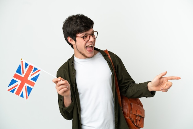 Young russian man holding an united kingdom flag isolated on white background pointing finger to the side and presenting a product