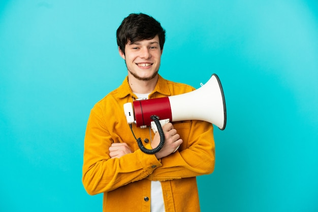 Young russian man isolated on blue background holding a megaphone and smiling