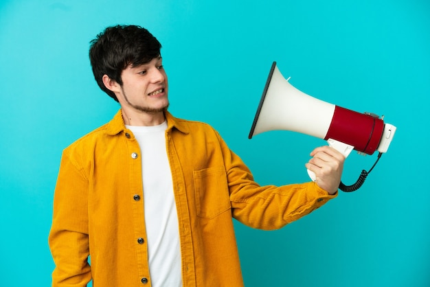Young russian man isolated on blue background holding a megaphone with stressed expression