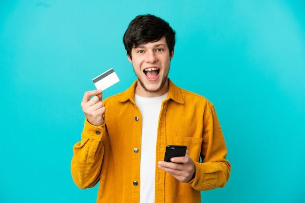 Молодой русский мужчина, изолированные на синем фоне, покупает с помощью мобильного телефона и держит кредитную карту с удивленным выражением лица