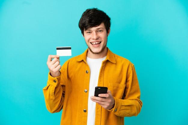 Молодой русский человек, изолированные на синем фоне, покупает с мобильного с помощью кредитной карты