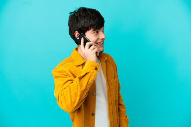 Молодой русский человек изолирован на синем фоне, разговаривая с кем-то по мобильному телефону