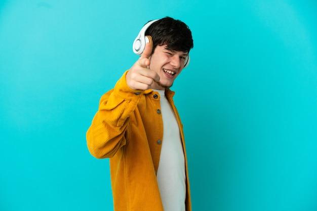 Молодой русский человек изолирован на синем фоне, слушает музыку и указывает вперед