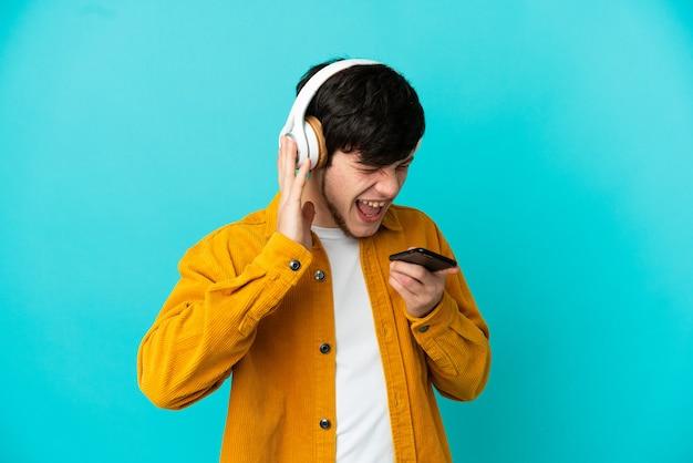 Молодой русский человек изолирован на синем фоне, слушает музыку с помощью мобильного телефона и поет