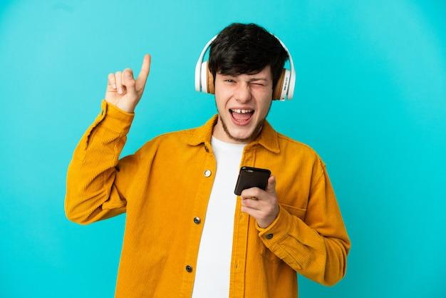 Молодой русский человек изолирован на синем фоне, слушая музыку с мобильным телефоном, делая рок-жест