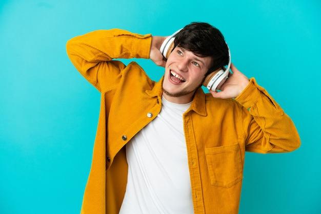 Молодой русский человек изолирован на синем фоне, слушает музыку