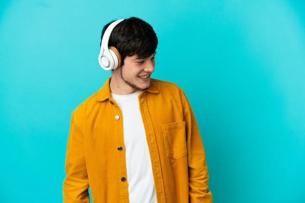 音楽を聴いて青い背景に分離された若いロシア人