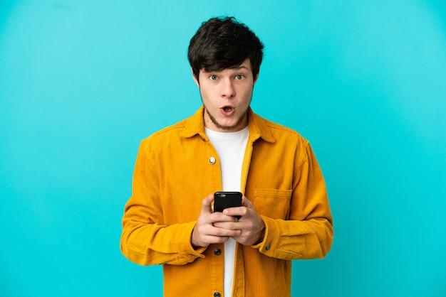 Молодой русский человек изолирован на синем фоне, глядя в камеру во время использования мобильного телефона с удивленным выражением лица