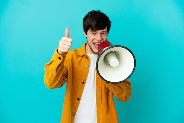Молодой русский человек изолирован на синем фоне, кричит в мегафон, чтобы что-то объявить, и с большим пальцем вверх