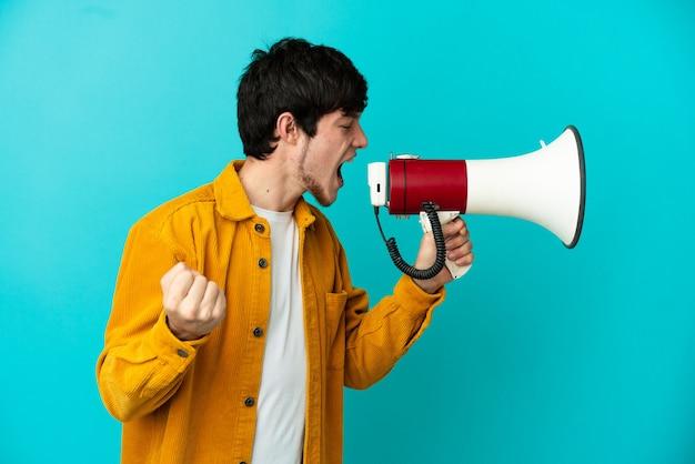 Молодой русский человек, изолированный на синем фоне, кричит в мегафон, чтобы объявить что-то в боковом положении