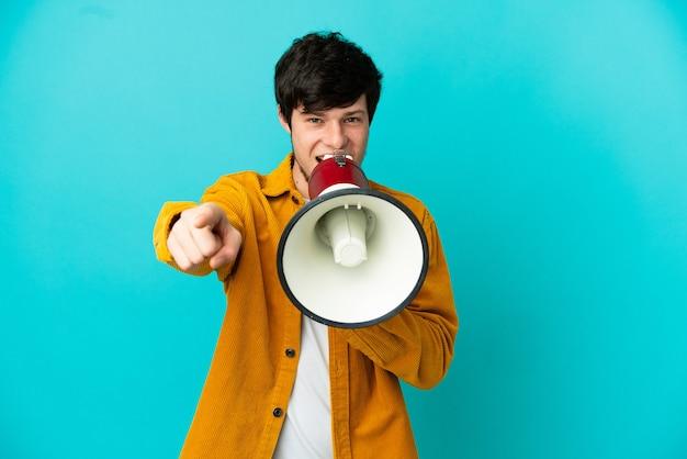Молодой русский человек изолирован на синем фоне, кричит в мегафон, чтобы что-то объявить, указывая на переднюю