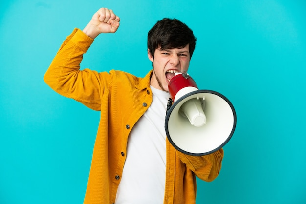 파란색 배경에 고립된 젊은 러시아 남자가 확성기를 통해 무언가를 발표하도록 외쳤다