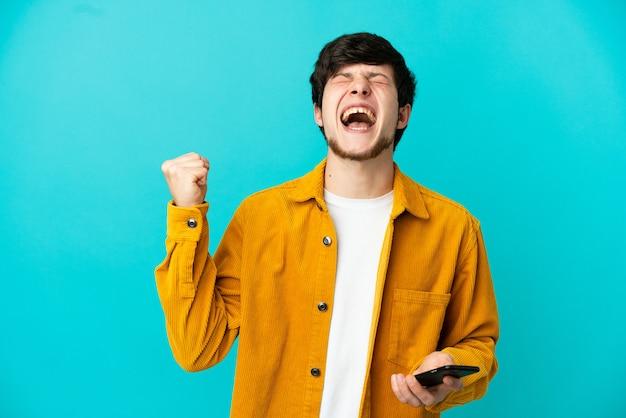 Молодой русский человек изолирован на синем фоне с помощью мобильного телефона и делает жест победы